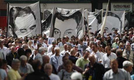 Banners bearing portraits of Bloody Sunday victims are carried to the Guildhall in Derry, where relatives were able to read the first copies of the Saville report, 15 June 2010