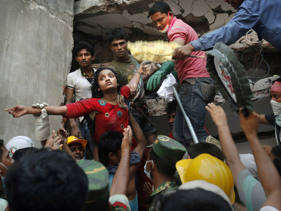A Bangladeshi woman survivor is lifted out of the rubble by rescuers at the site of a building that collapsed on Wednesday 24 April in Savar, near Dhaka, Bangladesh.