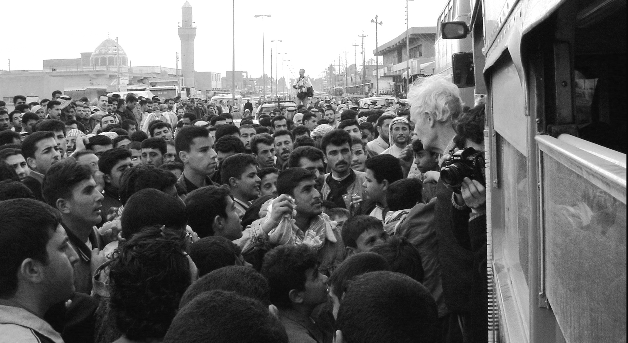Human shields from Britain are greeted as they cross the border into Iraq, February 2003